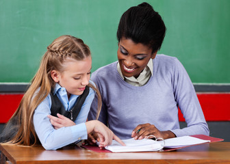 Teacher Assisting Schoolgirl At Desk