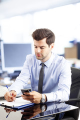 Young businessman reading a text message