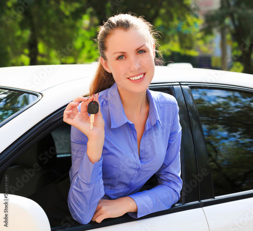 The happy girl showing the key of her new car