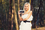 Beautiful adult girl with retro photo camera