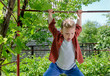 Happy young boy swinging on a metal bar