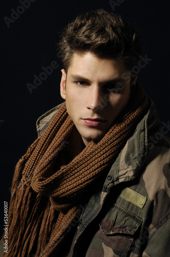 young man with cold wearing a scarf on black