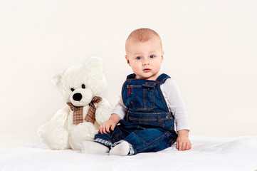 the little boy in blue overalls plays with a teddy bear