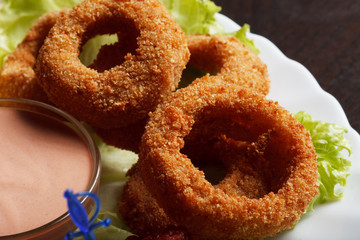 Image of meat breaded rings served with sauce