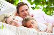 Family Relaxing In Beach Hammock With Sleeping Daughter