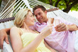 Couple Relaxing In Beach Hammock Drinking Champagne