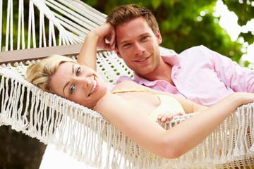 Couple Relaxing In Beach Hammock