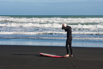 man preparing for surfing on Piha beach