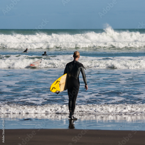 surfer on beach in New Zealand