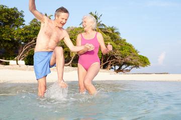 Senior Couple Splashing In Sea On Tropical Beach Holiday
