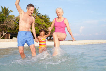 Grandparents With Granddaughter Splashing In Sea On Beach