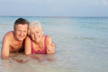 Romantic Senior Couple Lying In Sea On Beach Holiday