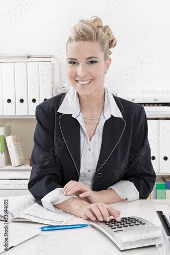 Lachende junge Frau tippt auf einem Taschenrechner im Büro