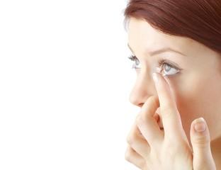 Frau setzt Kontaktlinse ein (weisser Hintergrund)