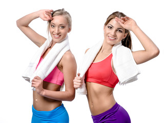 Two beautiful girls after workout with towels