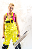 Tired female construction worker with putty knife working indoor poster
