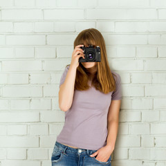 Young girl taking picture with a old vintage camera