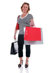 Mature female shopper carrying shopping bags isolated.