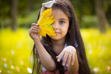 Cute hispanic girl  hiding over yellow leaf