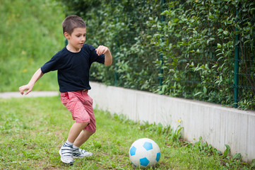Young kid playing soccer.