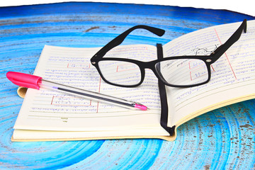 Glasses, notebook and pen on the homework