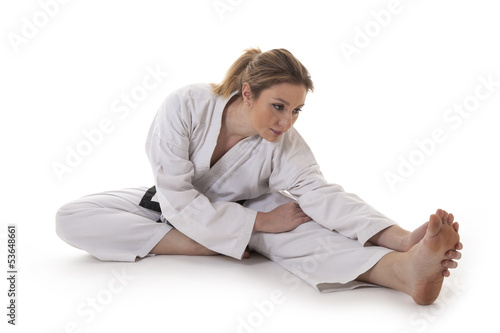 Blonde martial arts girl in kimono exercising karate.