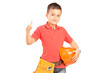 Child with tool belt holding a helmet and giving a thumb up