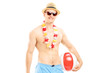 Fit man in swimming shorts, holding a beach ball