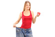 Happy weight loss female holding her old jeans and apple
