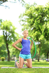 Female athlete on an exercising mat holding a hula hoop