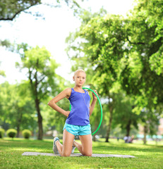 Female athlete on an exercising mat holding a hula hoop in a par