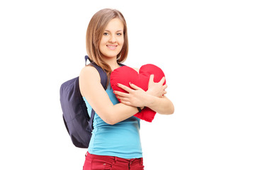 Female student with backpack holding a red heart