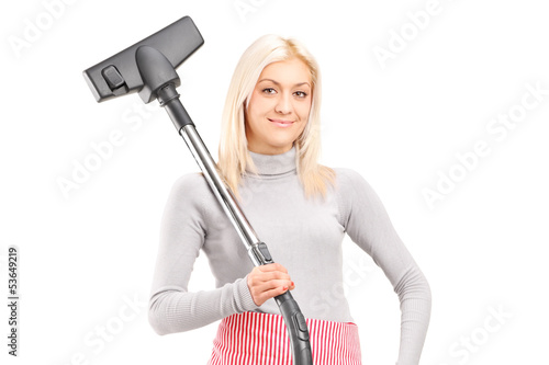 Blond housewife holding a vacuum cleaner
