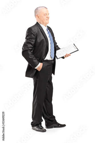 Full length portrait of a mature businessman posing with clipboa