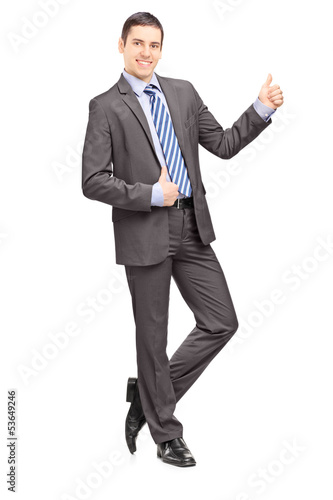 Young businessman leaning against wall and giving thumb up