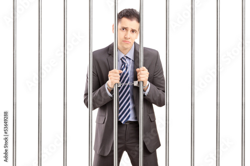 Sad handcuffed businessman in suit posing in jail