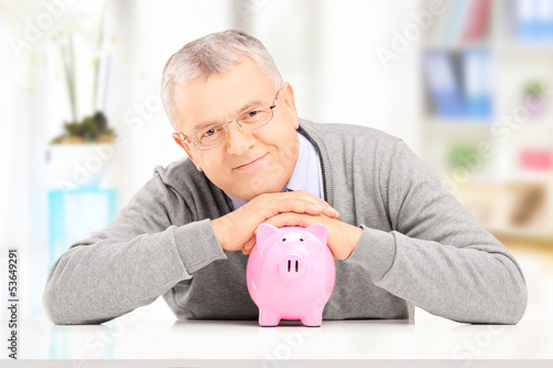 Satisfied gentleman posing over a piggy bank at his home