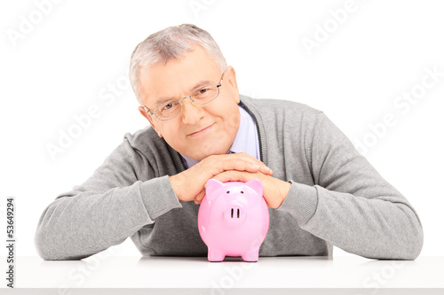 Satisfied mature gentleman posing over a piggy bank