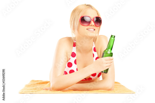 Smiling beautiful female lying on a towel and drinking beer