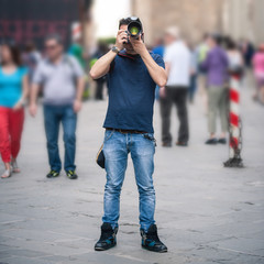 Young man taking photo with professional camera