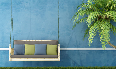 Vintage wooden swing against blue wall