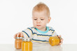 Boy with little jars of baby food, on a gray background