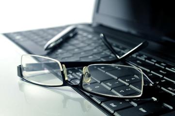 Brille und Kugelschreiber auf Laptop