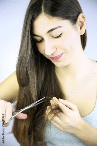 Beautiful girl cutting split ends of long hair