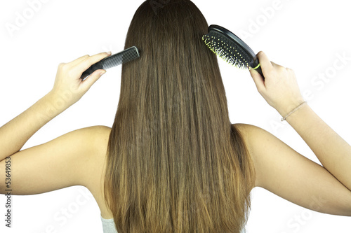 Woman with beautiful shiny hair with comb and brush in hands