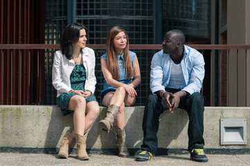 Group of three friends talking together outdoors on a bench.