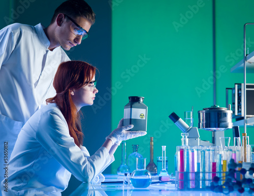 scientists with toxic waste container