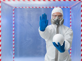 person in biohazard suit warns against contaminantion