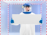 person in protective suit holding white board