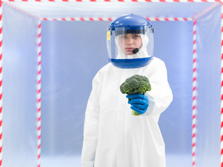 person in protective suit presenting a vegetable